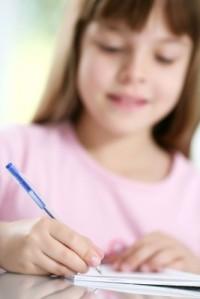 girl writing (blurry background)